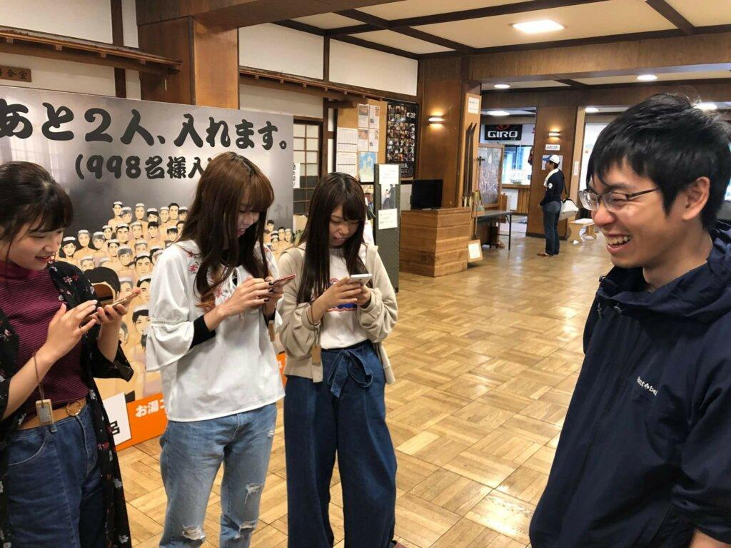 酸ヶ湯温泉旅館スタッフの説明を熱心に(スマホを使って)メモする学生たち