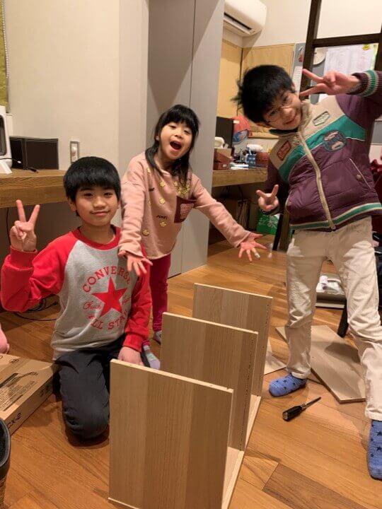 子ども部屋用の本棚を協力して組み立てる3人兄弟